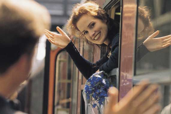 Young woman on a train waving goodbye.