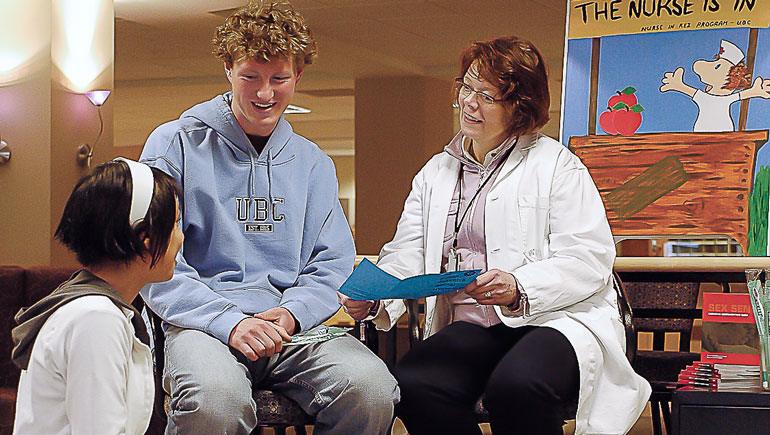 Two students talking to a residence nurse.