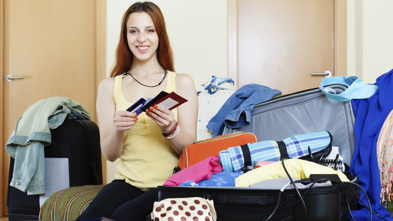 Young woman packing a suitcase.